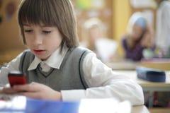 Het overseinen van de de leerlingstekst van de school op celtelefoon in klasse stock afbeelding