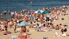 Het overvolle de zomerstrand, mensen zonnebaadt in de zon royalty-vrije stock fotografie