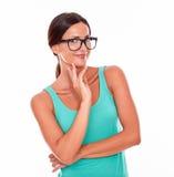 Het overwegen van donkerbruine vrouw met groen mouwloos onderhemd Stock Fotografie