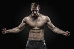 Het overweldigen van de spiermens die perfecte abs, schouders, bicepsen, triceps, borst tonen stock afbeeldingen