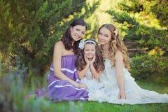 Het overweldigen van Donkerbruine blonde de zustersmeisjes die van kastanje blauwe ogen modieuze witte purpere kleding dragen die stock foto's