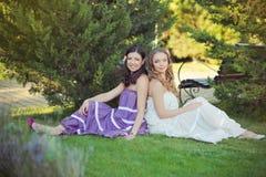 Het overweldigen van Donkerbruine blonde de zustersmeisjes die van kastanje blauwe ogen modieuze witte purpere kleding dragen die stock afbeeldingen