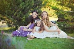 Het overweldigen van Donkerbruine blonde de zustersmeisjes die van kastanje blauwe ogen modieuze witte purpere kleding dragen die royalty-vrije stock foto's