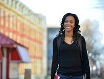 Het overweldigen van jonge Afrikaanse Amerikaanse vrouwelijke student op campus Royalty-vrije Stock Foto's
