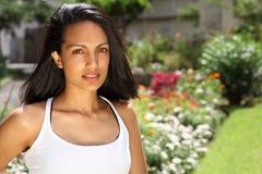 Het overweldigen van jonge vrouw in zonneschijn onder bloemen Stock Foto's