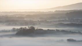 Het overweldigen van mistig Engels landelijk landschap bij zonsopgang in de Winter met Royalty-vrije Stock Afbeelding