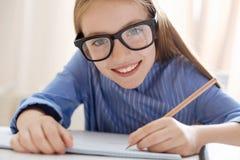 Het overweldigen van optimistisch meisje die glazen dragen terwijl het bestuderen Stock Afbeeldingen