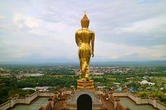 Het overweldigende goud kleurde het beeld van Boedha in het lopen houding die de stad van Nan, Wat Phra That Khao Noi-tempel, Tha stock foto