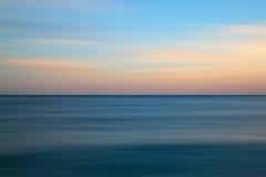 Het overweldigende lange beeld van het blootstellingszeegezicht van kalme oceaan bij zonsondergang Stock Foto