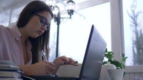 Het overwerk in studie, de vermoeide bril van de studentenvrouw gebruikt laptop computer aan het voorbereidingen treffen voor exa stock footage