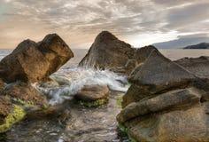 Het overzees, de zon, wolken, stenen Royalty-vrije Stock Afbeelding