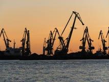Het overzees en de silhouetten van kranen in de zeehaven Royalty-vrije Stock Afbeelding