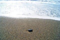 Het overzees en de zwarte steen in het zand royalty-vrije stock afbeeldingen