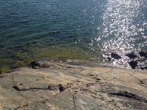 Het overzees ontmoet rotsen in zonbezinningen Stock Afbeeldingen