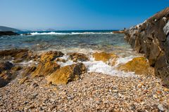 Het overzees slaat op de rotsen duidelijk water op de kust stock fotografie