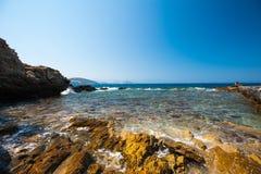 Het overzees slaat op de rotsen duidelijk water op de kust royalty-vrije stock foto
