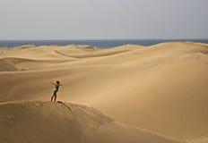 Het overzees van de duinenmeningen van het zand met een vrouw die op het vliegen Stock Fotografie
