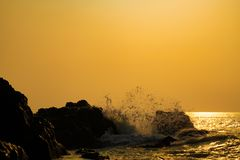 Het overzees van het de zonsopgangstrand van golven hittinng rotsen royalty-vrije stock afbeeldingen