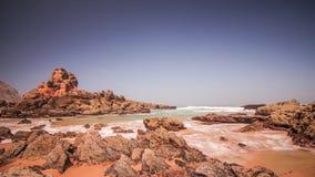 Het overzees van het ochtendgetijde op rotsachtige strandachtergrond Overzeese golven op rotsachtig strand stock videobeelden