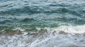Het overzeese oceaanwater wast de zandige, rotsachtige kust stock footage