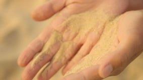 Het overzeese zand wordt gegoten van vrouwen` s handen stock video