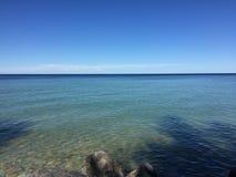 Het overzien van een groot meer met bomen en zand onderaan stock afbeelding
