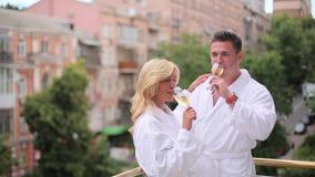 Het paar in badjassen drinkt champagne stock videobeelden