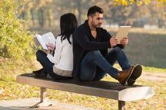Het paar bekijkt een een Tablet en Boek van Digtial stock foto