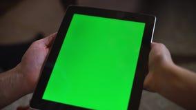 Het paar bekijkt het groene scherm ipad op Kerstmisvooravond stock video