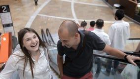 Het paar beklimt de roltrap en bewondert de buitenkant van het winkelcentrum stock videobeelden
