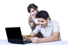 Het paar betaalt online gebruikende geïsoleerde creditcard - royalty-vrije stock foto