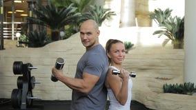 Het paar bodybuilders stelt voor de reclamefoto in de luxegymnastiek stock video