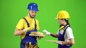 Het paar bouwers kiest houten raad Het groene scherm stock video