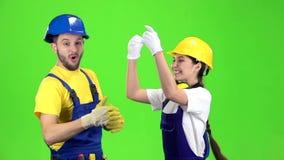 Het paar bouwers is tevreden met de overwinning in de offerte voor de bouw van een nieuwe supermarkt Het groene scherm stock video