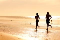 Het paar dat van de sport op het strand aanstoot royalty-vrije stock foto's