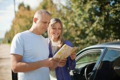 Het paar dat van de toerist de kaart op de weg bekijkt Stock Foto's