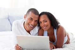 Het paar dat van Romantice laptop met behulp van stock foto's