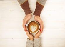 Het paar in de kop van de liefdeholding van coffe in handen op houten hoogste mening als achtergrond, wijnoogst stemde beeld Royalty-vrije Stock Foto