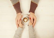 Het paar in de kop van de liefdeholding van coffe in handen op houten hoogste mening als achtergrond, wijnoogst stemde beeld Royalty-vrije Stock Afbeelding