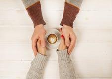 Het paar in de kop van de liefdeholding van coffe in handen op houten hoogste mening als achtergrond, wijnoogst stemde beeld Stock Foto