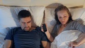 Het paar die delend afstandsbediening, die op TV letten ruzie maken stock footage