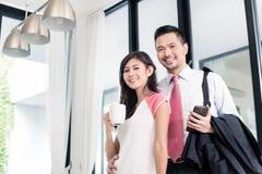 Het paar die ontbijt hebben vóór de mens gaat naar bureau Stock Foto