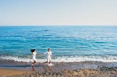 Het paar die rond op het strand lopen royalty-vrije stock fotografie