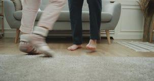 Het paar die van de huisstijl in de woonkamerclose-up dansen die benen vangen stock footage