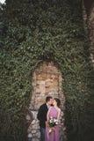 Het paar die van het luxehuwelijk en op de schitterende installaties koesteren kussen als achtergrond, holt dichtbij oud kasteel  Royalty-vrije Stock Fotografie