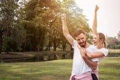 Het paar die van het uitdagingssucces handen voor de voltooiing van het geschiktheidsdoel opheffen stock fotografie