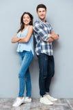Het paar die zich met wapens bevinden kruiste over grijze achtergrond royalty-vrije stock fotografie