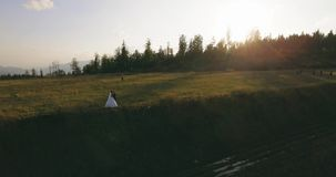 Het paar die zich op de schilderachtige berg op de zonsopgang bckg 4k antenne bevinden stock videobeelden