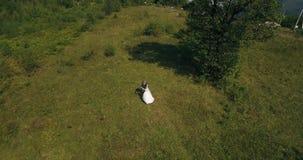 Het paar die zich op de schilderachtige berg op de zonsopgang bckg 4k antenne bevinden stock footage