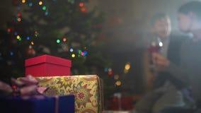 Het paar drinkt wijn dichtbij de verfraaide Kerstboom stock footage